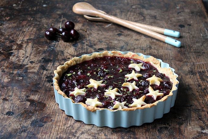 A pie made with fresh cherries with pastry stars on top and lime zest.