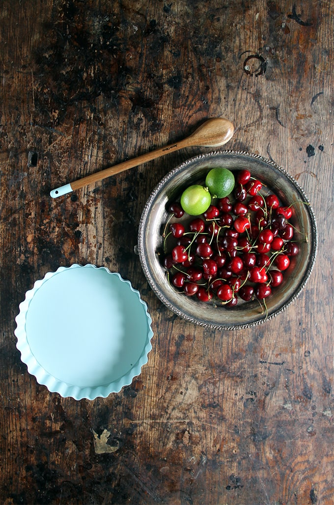 A bowl of fresh cherries and a lime on a vintage plate, ready to be made into cherry pie.