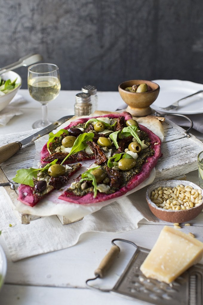 Beet Pizza with Beet Leaf Pesto. A bright purple vegan pizza dough that's super easy to make and tastes delicious. Topped with capers, olives and sun dried tomatoes for loads of flavour. Shown on a table set for two with wine and salad.