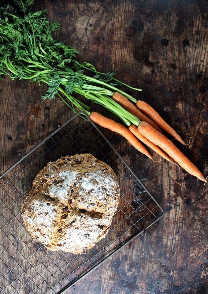 Cinnamon Carrot Soda Bread on a cooling rack next to a bunch of carrots.