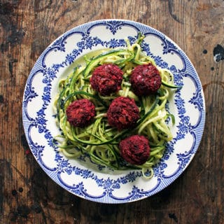A close up of a plate of zoodles and meatballs.