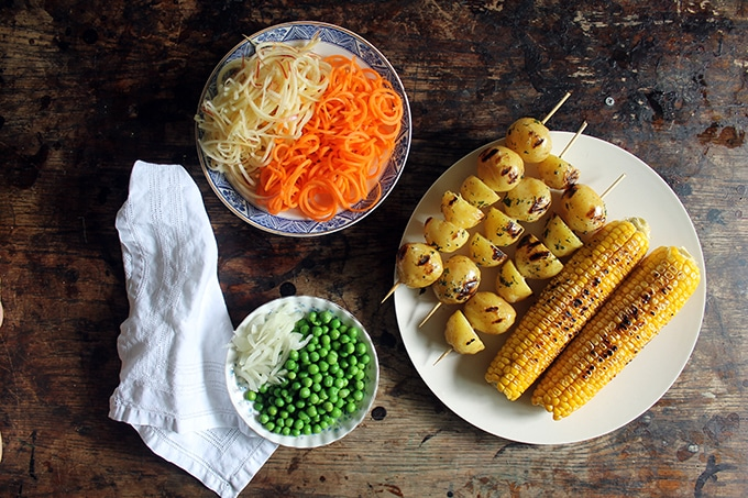 Ingredients for a Brazilian Gaucho Potato Salad - a dish of spiralized apple and carrot, peas and onion, grilled corn and potatoes