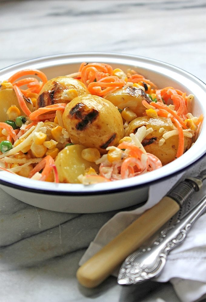 A bowl of Brazilian potato salad, with charred potatoes and corn, spiralized carrots and apple and peas and carrot in a creamy dressing. Gluten free and easily vegan.