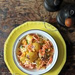 Salad on a plate, with potatoes, apple and carrots.