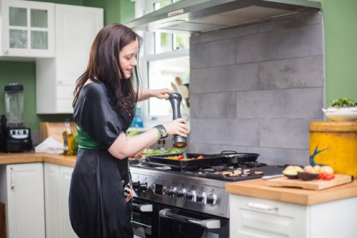 A woman cooking in a kitchen.