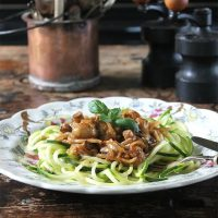 Miso Roasted Mushrooms and Courgetti/Zoodles on a plate in front of a copper pot of cutlery