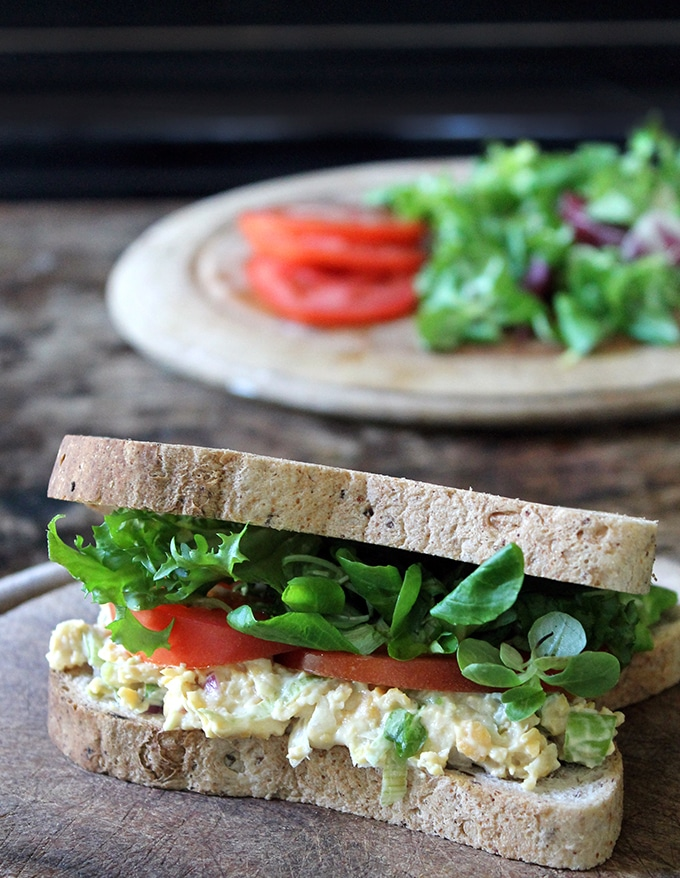 A vegan tuna mayo sandwich on a bread board, with lettuce and tomato. The vegan tuna is made from chickpeas.