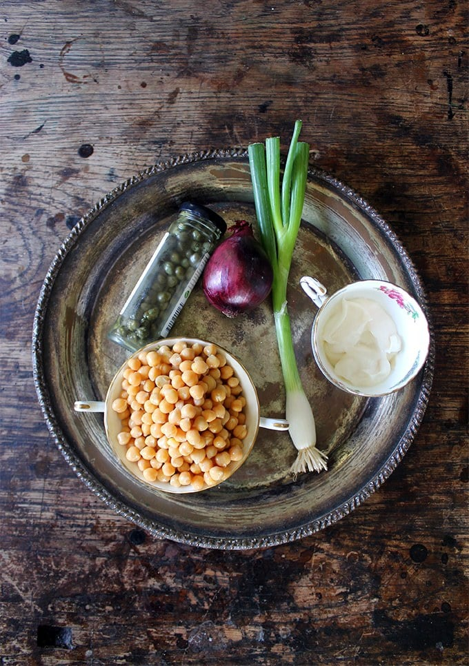Silver tray on a table with ingredients to make a Vegan Tuna Mayo Sandwich - chickpeas, capers, red onion, spring onion/scallion, mayonnaise