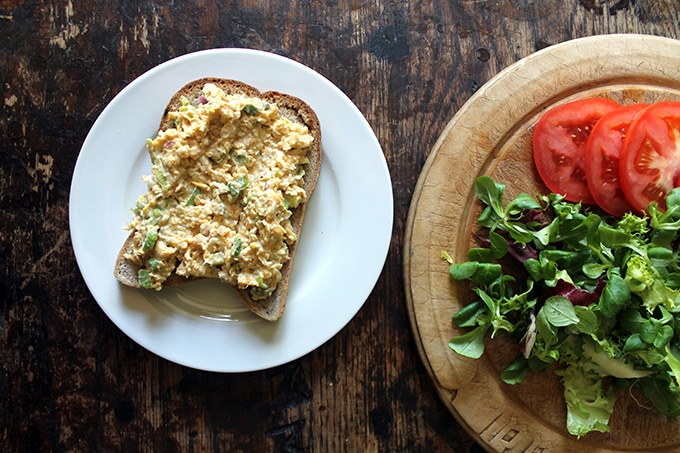 A slice of bread on a plate spread with vegan tuna salad (chickpea/garbanzo based) with a breadboard covered in lettuce and sliced tomatoes.