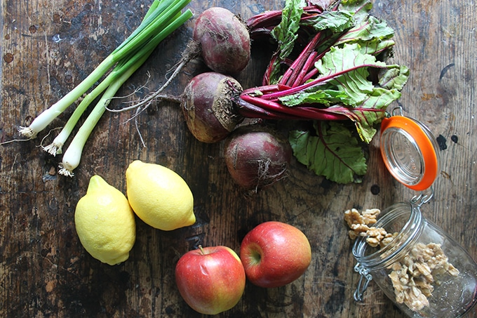 Flat lay of ingredients for Beetroot Salad: scallions, beets, lemon, apples, walnuts.