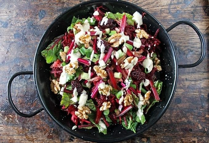Blackberry Apple Beet Salad with Tahini Dressing in a black serving dish on wooden table.