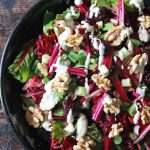 Close up of serving dish of beet salad with walnuts.