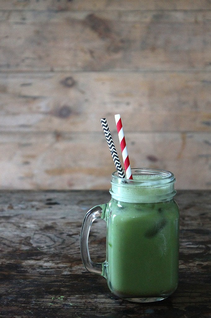 A glass of green matcha horchata. A matcha twist on the classic Mexican horchata vegan drink. Shown on wooden background with paper straws.