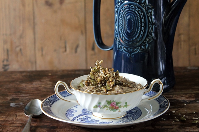 A bowl of oatmeal and vintage coffee pot sitting on top of a wooden table