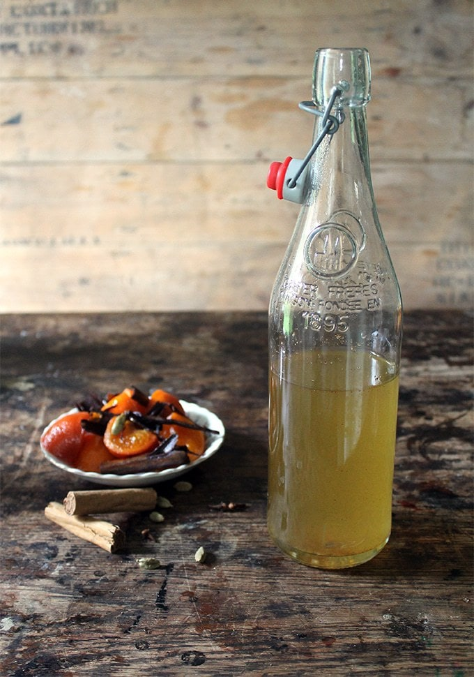 A bottle of spiced Mulled Simple Syrup for making Mulled Gin Cocktail recipe. Perfect as an edible christmas gift. Shown in front of a wooden crate with a dish of oranges and spices.