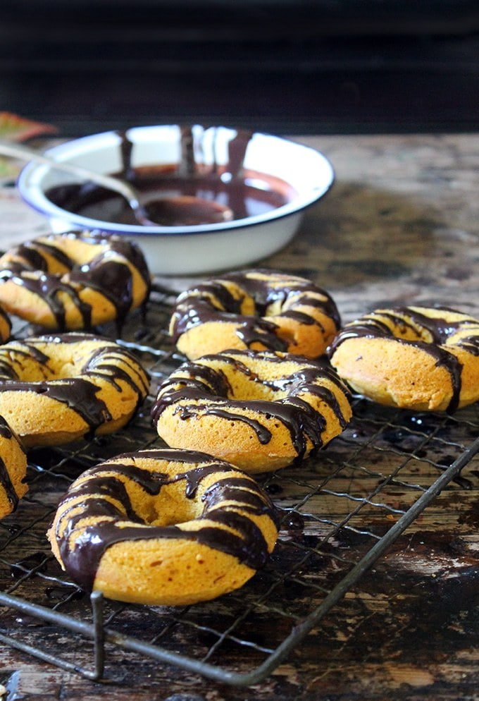 Cooling rack with pumpkin donuts drizzled with chocolate. Bowl of melted chocolate in the background.