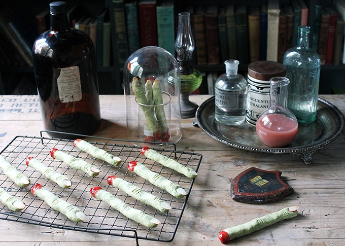 A spooky table with a rack of witch fingers cookies, science beakers and jars of potions. Perfect Halloween party food.