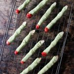 Rows of naturally green peanut butter Witch Finger Cookies that look scary - perfect for a Halloween party food.