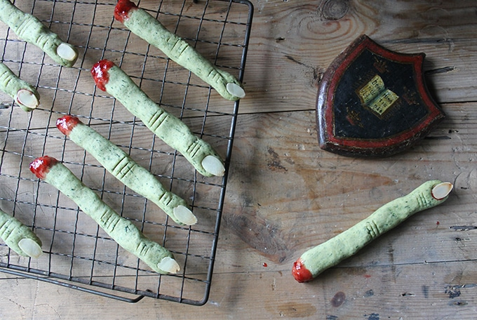 Naturally Green Peanut Butter Witch Finger Cookies on a cooling rack, with almond slivers for fingernails and jam to look like blood at the end of the severed finger. Gruesome Halloween party food!