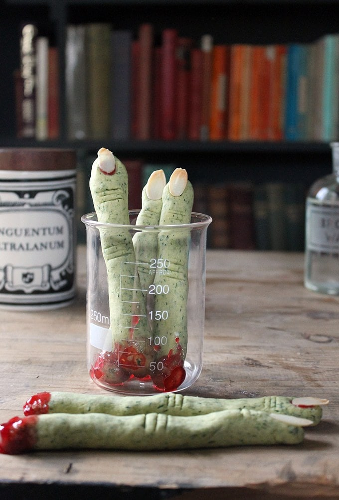 A science beaker filled with green cookies shaped like fingers.