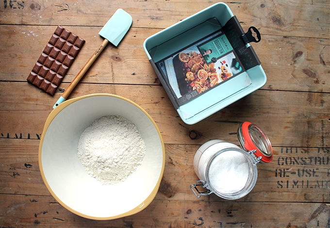 Making a cake, with flour in a bowl, jar of sugar and cake pan.