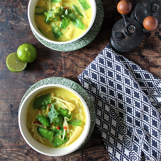 Easy Vegan Laksa in bowls on a wooden table with sliced limes