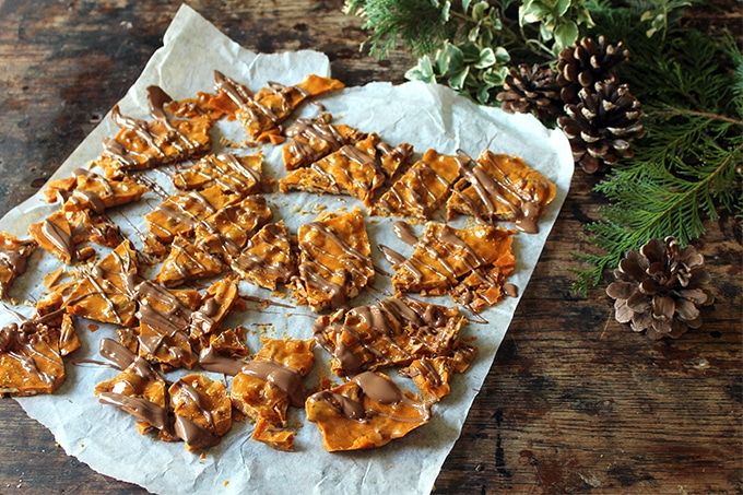 Ginger Pecan Brittle with Chocolate Drizzle recipe. Shards of this easy to make candy are shown on a white baking paper on wooden table next to pine cones and christmas greens
