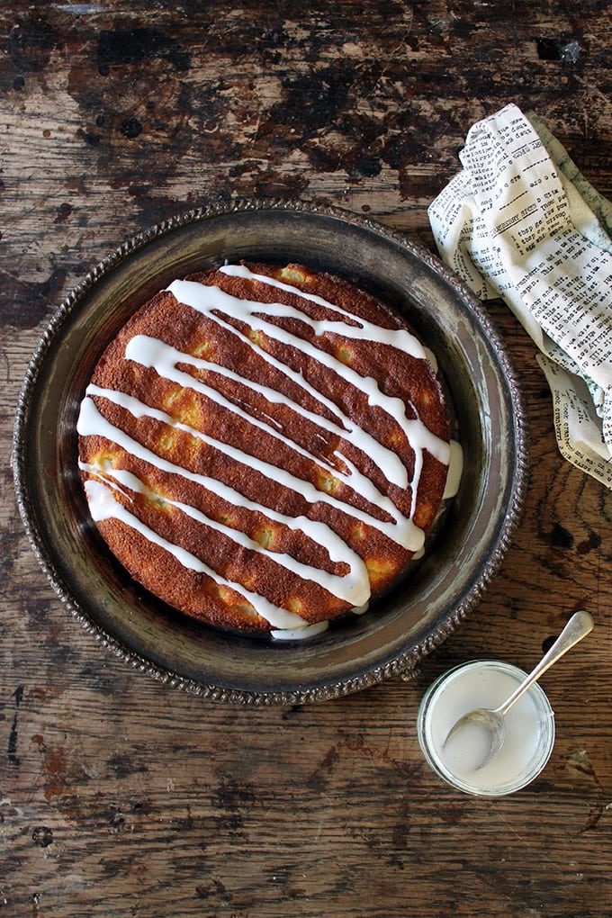 Overhead shot of a Gluten-free Ginger and Pear Polenta Cake recipe with a pear drizzle. Shown on a vintage platter and wooden table.