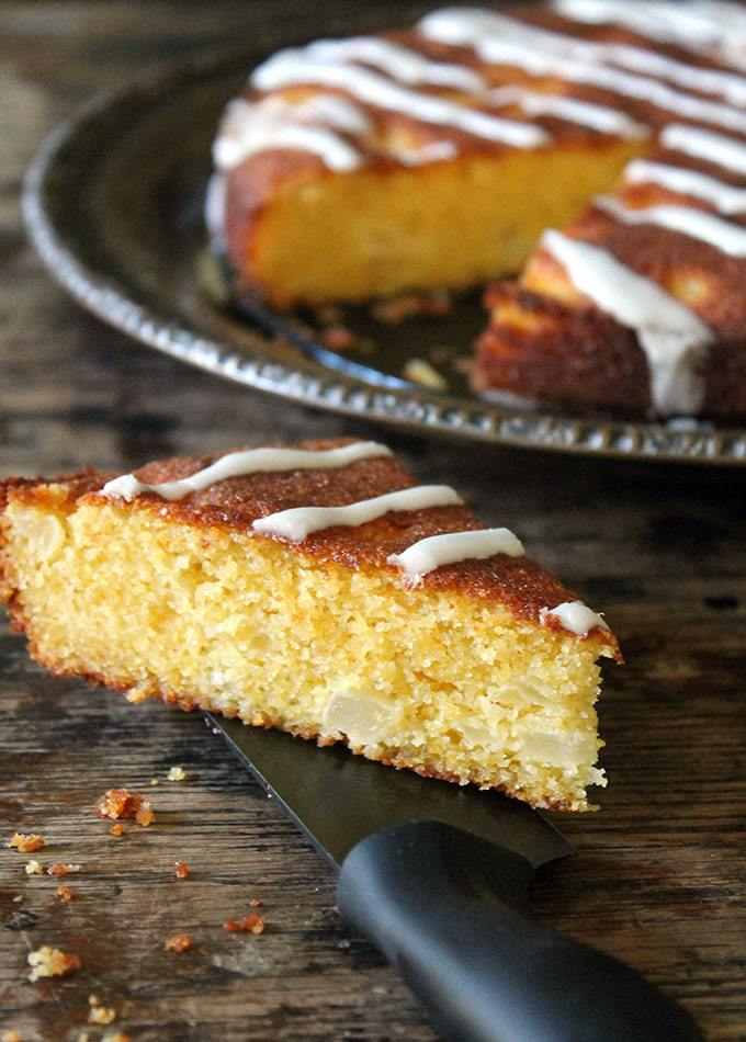 A slice of one bowl Gluten free Ginger and Pear Polenta Cake with a ginger drizzle. On a wooden table next to the cake on a vintage silver platter.