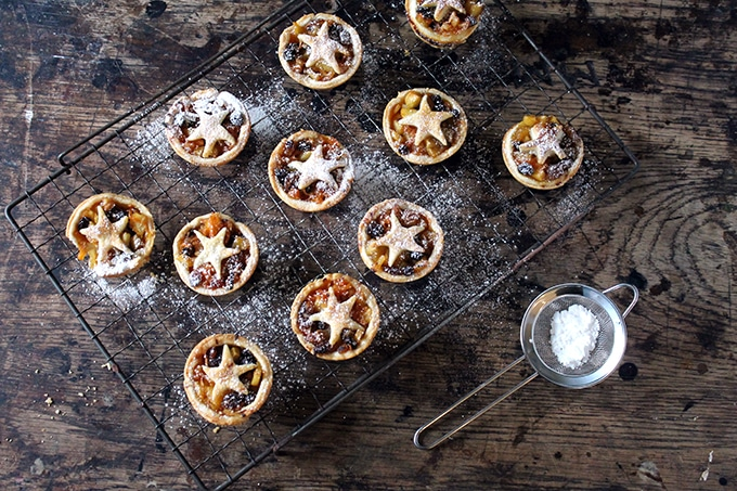 Healthy Carrot and Apple Mince Pies on a vintage cooling rack next to a small sieve of powdered sugar.