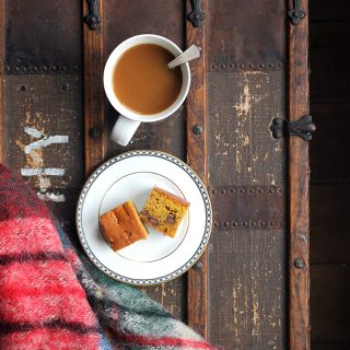 A plate of cake and a mug of tea on a wooden table.