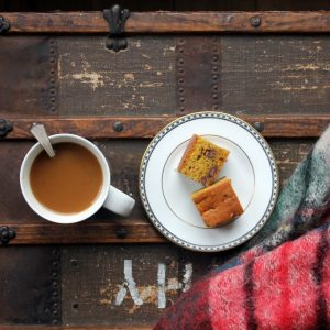 A plate of cake sitting on top of a wooden table, with a mug of tea.