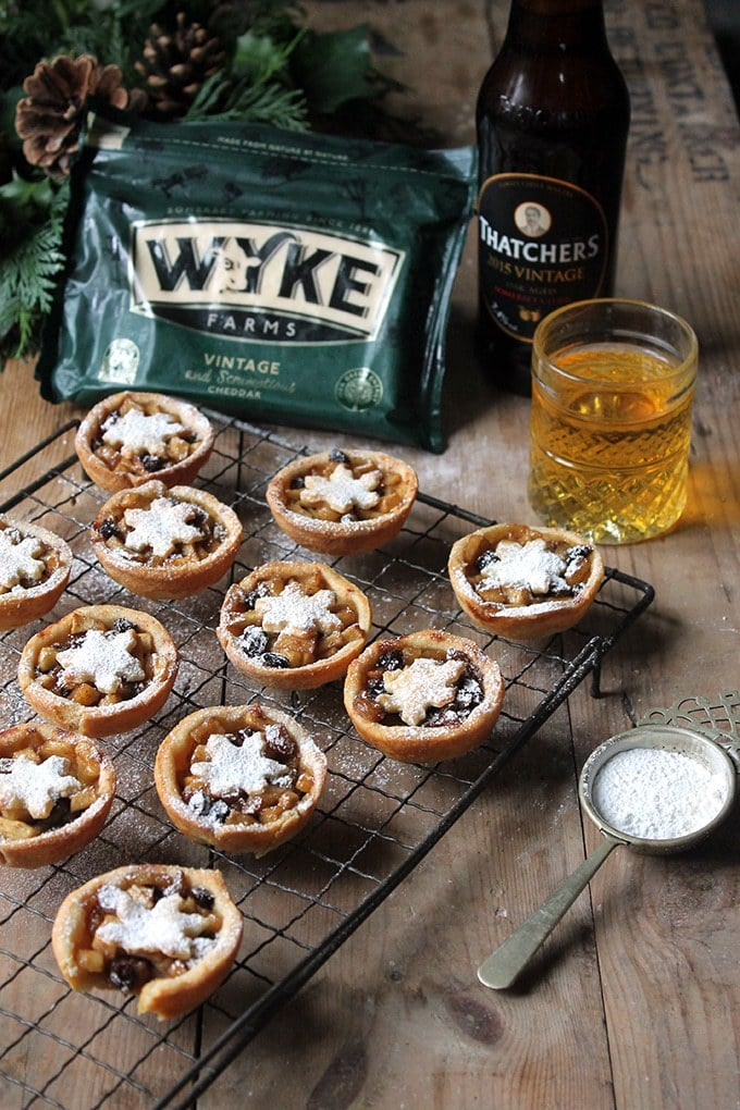 Sweet Apple and Cider Mince Pies with Cheddar Pastry on a cooling rack with a bottle and glass of apple cider and packet of cheese in the background.