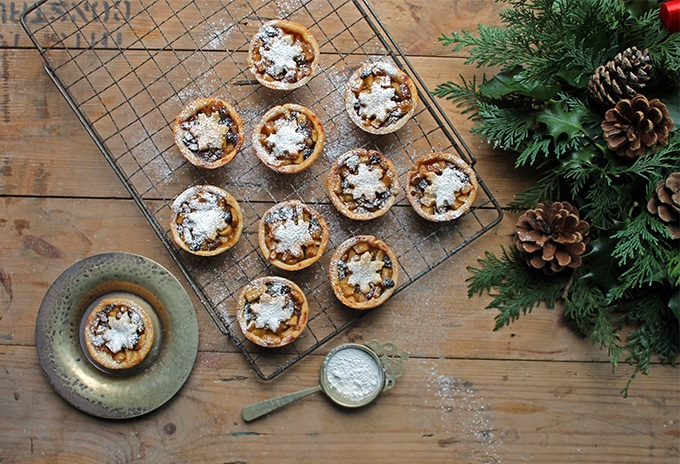 Sweet Apple and Cider Mince Pies with Cheddar Pastry on a cooling rack next to pine branches and pine cones.