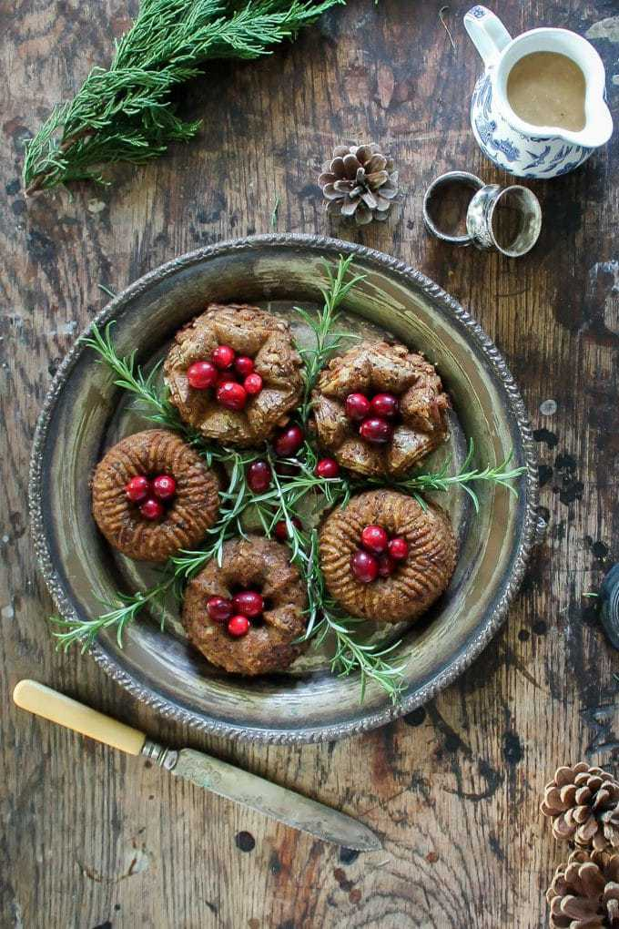 Overhead shot of a silver platter with six mini chestnut vegan and vegetarian nut loaf shown with sprigs of rosemary and fresh cranberries on top.