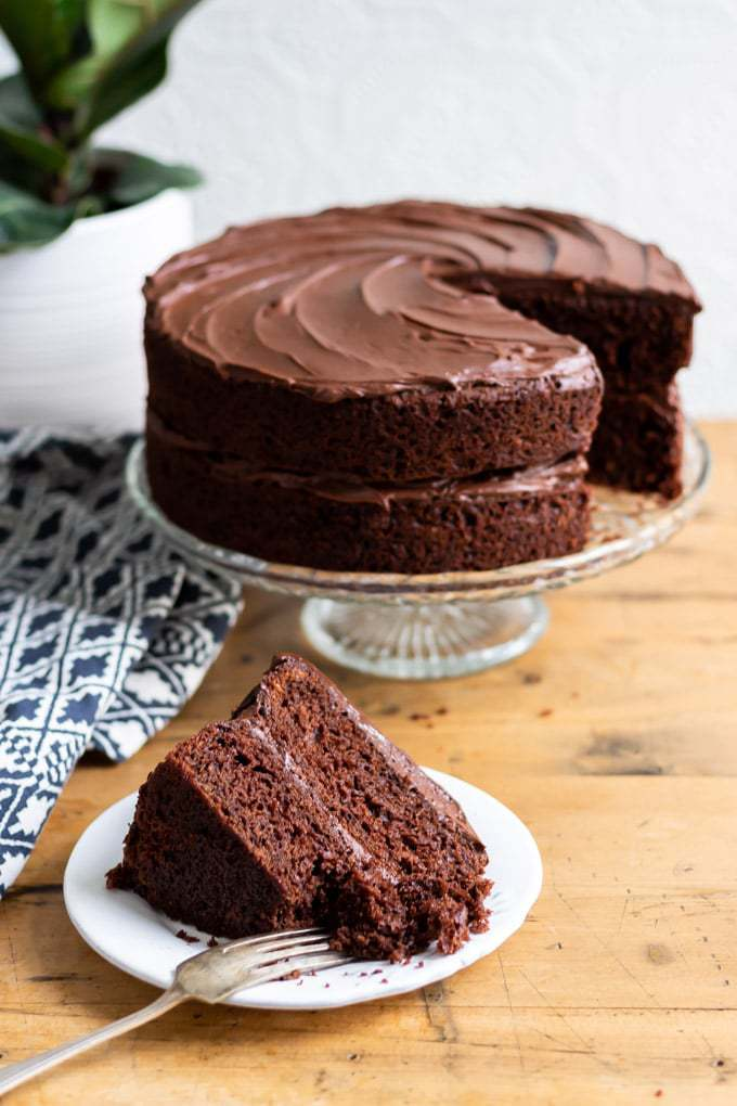 The BEST Vegan Chocolate Cake recipe. A slice of cake in front of the vegan layer cake on a cake stand.