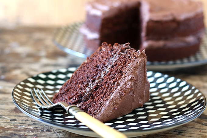 Close up of a slice of vegan chocolate cake, which is moist, fluffy and easy to make! It's perfect as a vegan birthday cake or for any occasion.