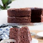 A slice of easy vegan chocolate cake recipe in front of a vegan cake on a cake stand with vegan frosting.