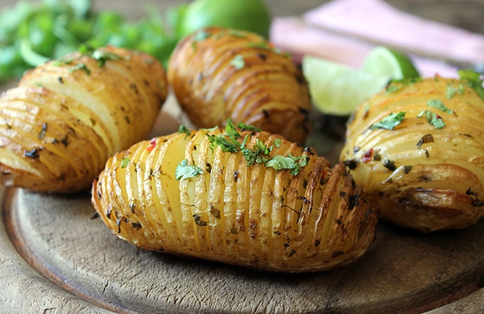 Hasselback Potatoes with Chilli and Lime. Hasselback potatoes are easy to make, but extra-special. The layers get lovely and crispy, while the base has that beautifully soft baked potato texture. You can dress them in many different ways, with herbs, garlic and even flavoured salt, but I really love them with a little kick from this zingy chilli, coriander (cilantro) and lime butter.