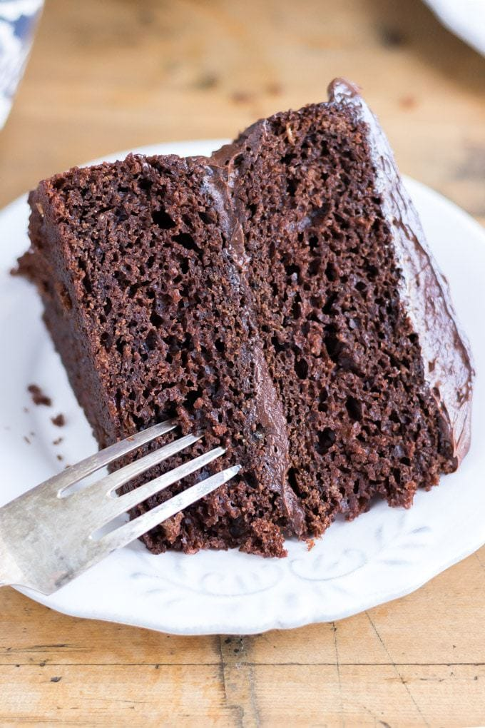 Close up of a slice of two layer chocolate vegan cake on a white plate with vintage fork. Get the vegan cake recipe now.