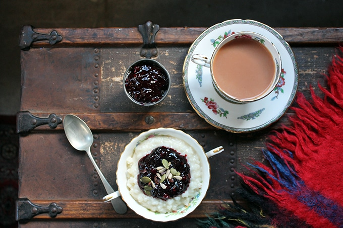 A table with a bowl of rice pudding and tea in a vintage teacup.