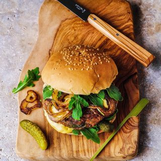 Burger on a wooden cutting board, with a pickle and knife next to it.