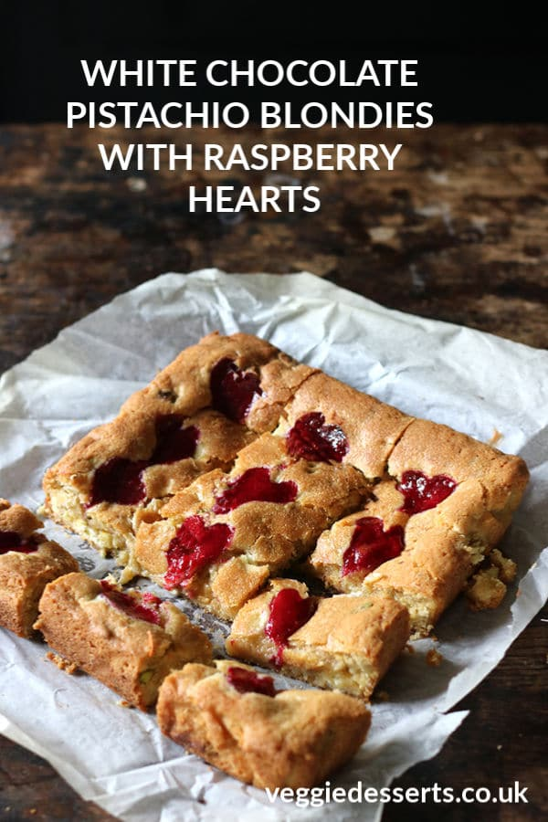 These pistachio blondies with white chocolate are decadent, chewy and delicious. They have crunch from chopped pistachios, sweetness from white chocolate and the sharp raspberry puree is swirled into hearts. Perfect for Valentine's Day! Serve alone or topped with vanilla ice cream.#valentinesday #valentinesdaydessert #blondies #pistachio #raspberrypuree #veggiedesserts