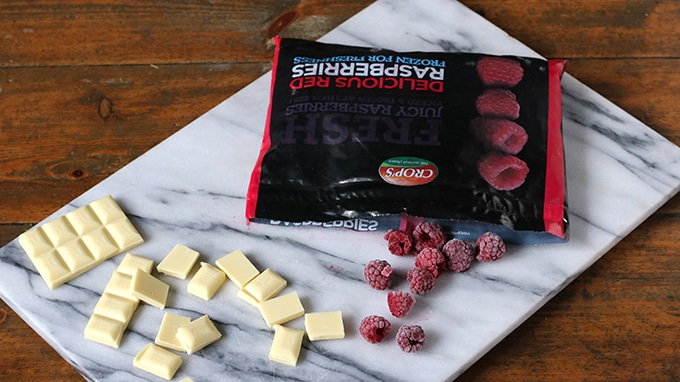 A bag of frozen raspberries next to squares of white chocolate on a marble cutting board.