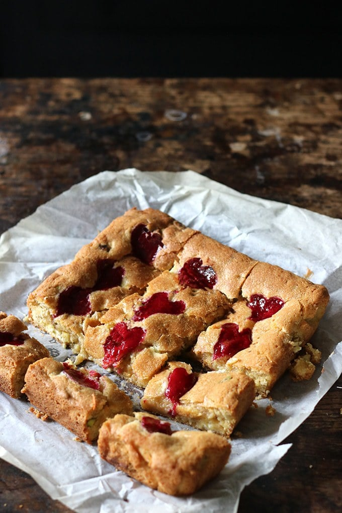 A slab of Pistachio Blondies with Raspberry Swirl Hearts with some cut into squares. On baking paper on a wooden table. Get the recipe.