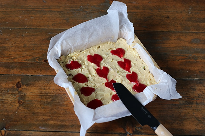 Blondie batter with spoonfuls of raspberry sauce being formed into heart shapes.