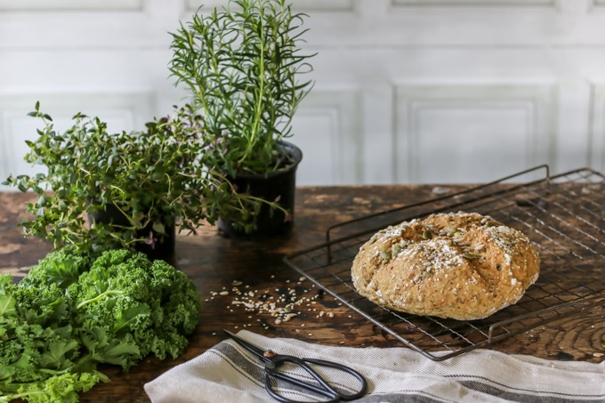 A loaf of seedy Irish soda bread cooling on a rack next to herbs for the sauteed herby greens.