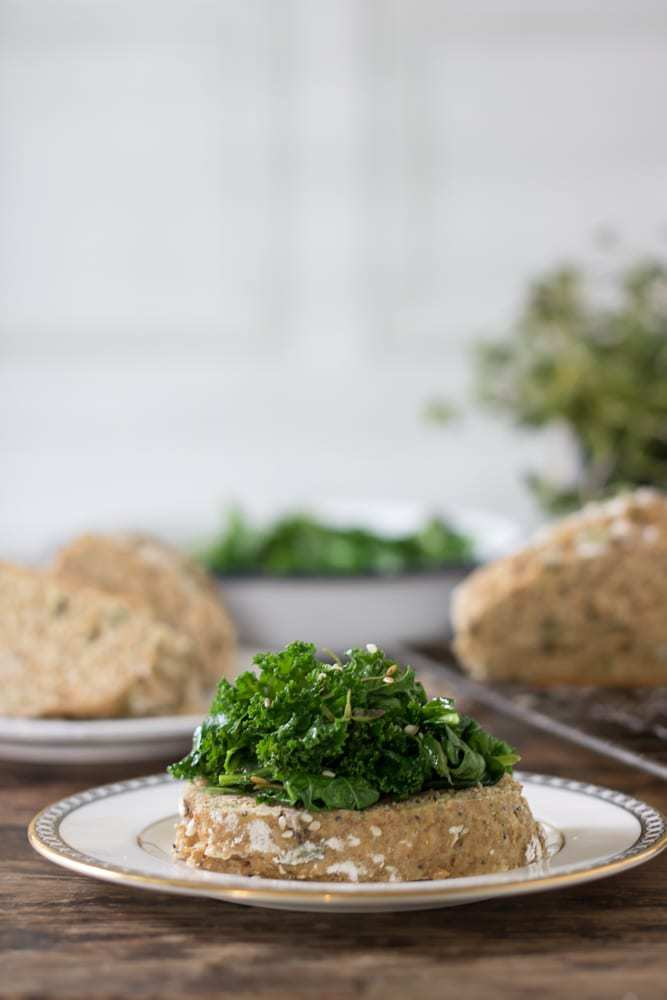 A slice of seedy soda bread topped with a pile of herby kale.