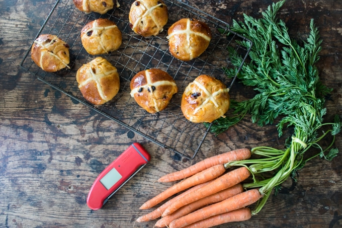 Carrot and Ginger Hot Cross Buns on a tray with a bunch of carrots and a Thermapen thermometer.