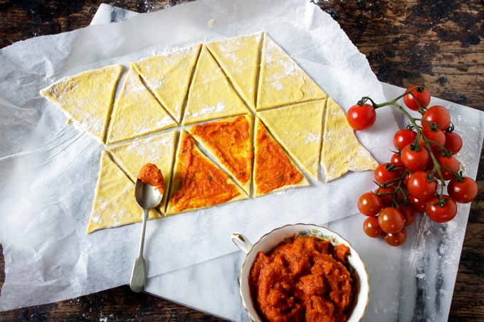 How to make carrot pizza: carrot pizza dough cut into triangles being spread with carrot tomato pizza sauce.